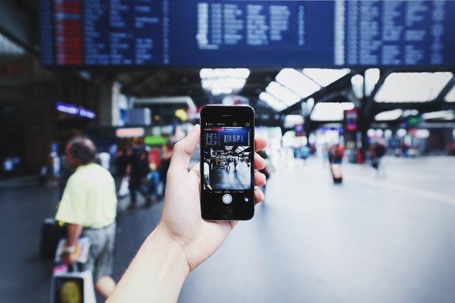 Človek, ktorý si fotí tabuľu odletov na mobil