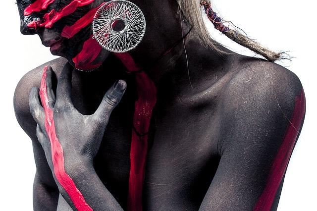 Žena s výrazne pomaľovaným telom s výraznými striebornými náušnicami