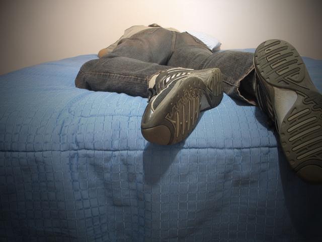 Človek leží na posteli, odpočinok