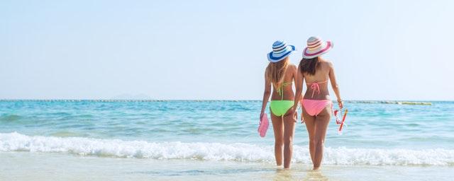 Dve ženy v plavkách kráčajú po pláži pri mori