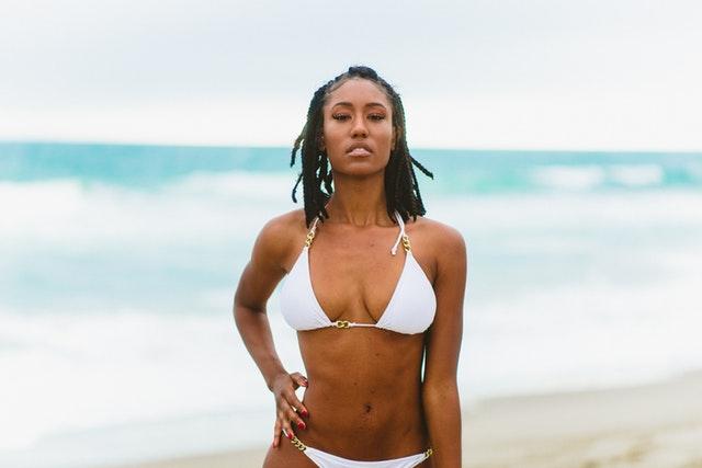 Žena s veľkým poprsím, v bielych plavkách stojí na pláži s rukou v bok