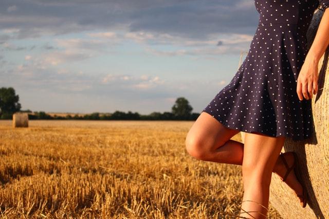 Dievča v modrých bodkovaných šatách je opreté o stoh slamy s pokrčeným kolenom