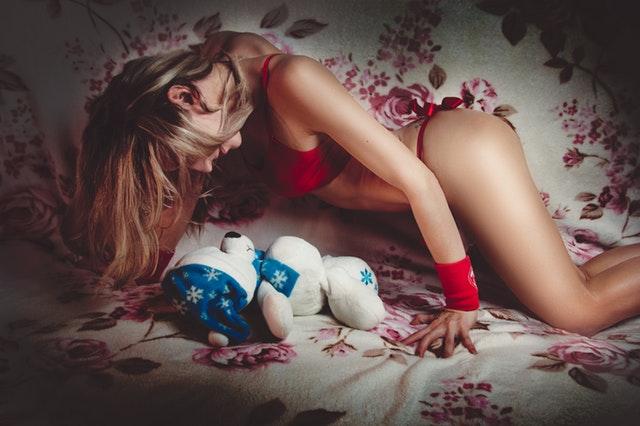 Žena s blond vlasmi a v červenej spodnej bielizni leží na posteli nad plyšovým medveďom.jpg