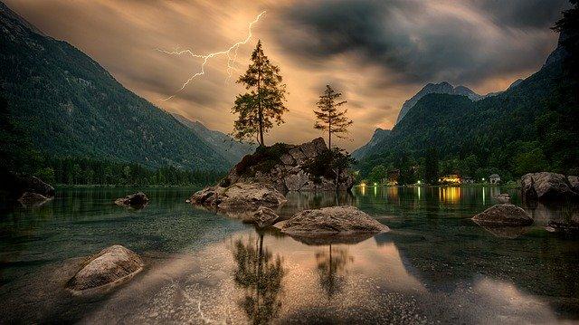 Ihličnaté stromy uprostred jazera, okolo ktorého svietia svetlá.jpg