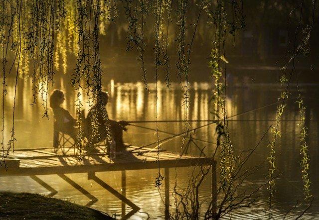 Muž a žena sedia na móle a lovia ryby pri západe slnka.jpg